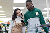 Female grocer helping male customer in supermarket