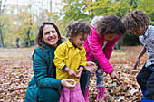 Portrait happy mother and children playing in autumn leaves