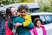 Happy mother and daughter hugging outside car