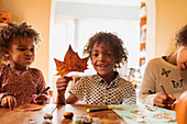 Boy with autumn leaf doing crafts with sisters at table