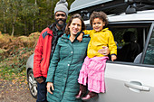 Portrait happy parents and toddler daughter outside car