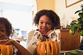 Portrait smiling girl carving pumpkin