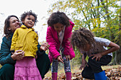 Happy mother and children playing in autumn leaves