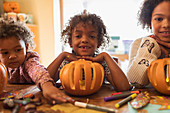 Portrait happy brother and sisters carving pumpkins at table