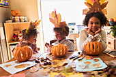 Brother and sisters with turkey hats carving pumpkins