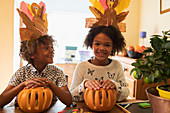 Happy brother and sister with turkey hats carving pumpkins