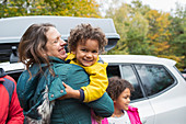 Happy mother holding daughter outside car in parking lot