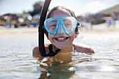 Happy girl wearing snorkel and goggles in ocean