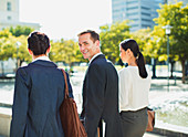 Smiling businessman walking with colleagues outdoors