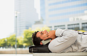 Businessman laying on briefcase and talking on cell phone