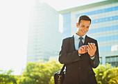 Businessman text messaging outside urban building