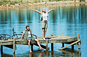 Exuberant woman with arms outstretched on dock over lake