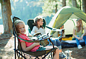 Smiling girl sitting in chair at campsite
