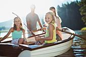 Smiling family in rowboat on lake