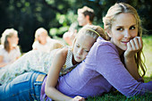 Serene mother and daughter laying in grass