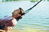 Serene man laying in hammock at lakeside