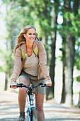 Smiling woman riding mountain bike in woods