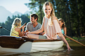 Smiling woman with family in rowboat on lake