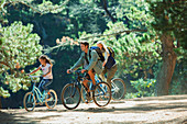 Family bike riding in woods