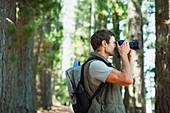 Man using digital camera in woods