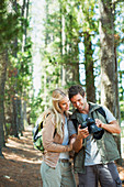 Smiling couple looking at digital camera in woods