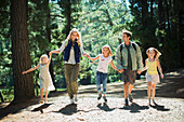 Smiling family holding hands and walking in woods