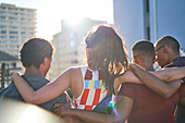 Young friends hugging and hanging out on rooftop balcony