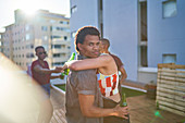 Young couple hugging and drinking beer on urban rooftop