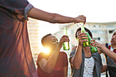 Young friends toasting beer glasses on sunny urban rooftop