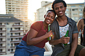 Portrait happy young couple drinking beer on urban rooftop