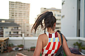 Carefree young woman dancing on urban rooftop