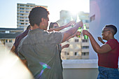 Young friends dancing and drinking beer on sunny rooftop