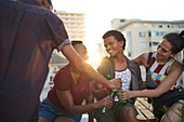 Young friends drinking beer on sunny urban rooftop balcony