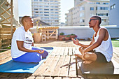 Young couple talking on yoga mats on sunny rooftop balcony