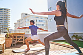 Young couple practicing yoga on sunny urban balcony rooftop