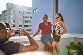 Happy young women friends posing for photo on sunny balcony