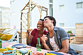 Happy young couple laughing and eating at patio table