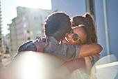 Happy young couple hugging on sunny urban balcony