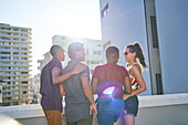 Young friends hanging out on sunny urban rooftop balcony