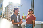 Happy young friends drinking beer on sunny rooftop balcony