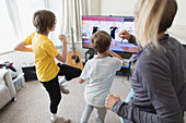 Family exercising at TV in living room