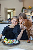 Portrait brothers with dog eating at dining table