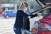 Woman in face mask loading groceries into car in parking lot