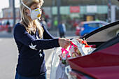 Woman in face mask loading groceries into car