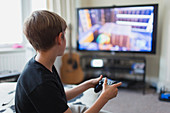 Boy playing video game at TV in living room