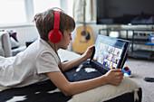 Boy with headphones and digital tablet homeschooling
