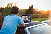 Man with headphones video chatting with friends on car roof
