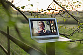 Friends video chatting on laptop screen on rural fence post