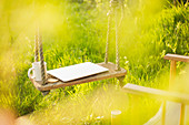 Laptop and coffee cup on swing in sunny garden