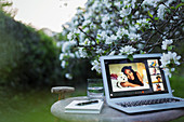 Friends video chatting on laptop screen in tranquil garden